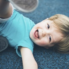 Little boy laughing on the floor.